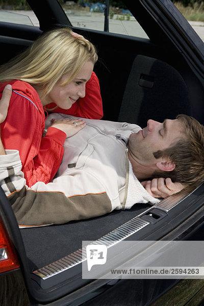 Ein Paar  das zusammen auf dem Rücksitz eines Autos liegt.