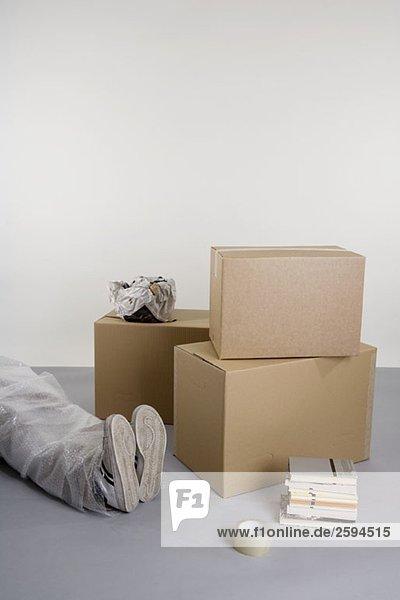 Gestapelte Schachteln und Bücher und ein in Luftpolsterfolie verpackter Körper