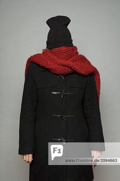 Eine junge Frau in Schal  Winterjacke und Strickmütze gebündelt