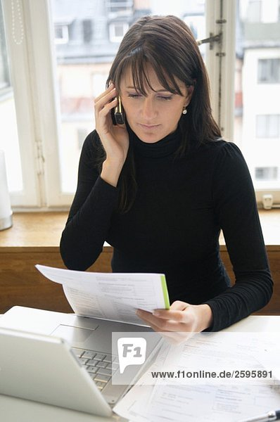 Frau liest und spricht auf ihrem Handy