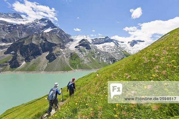 Hikers walking at lakeside  Hohe Tauern  Alps  Mooserboden Reservoir  Kaprun valley  Zell am See  Salzburg  Austria