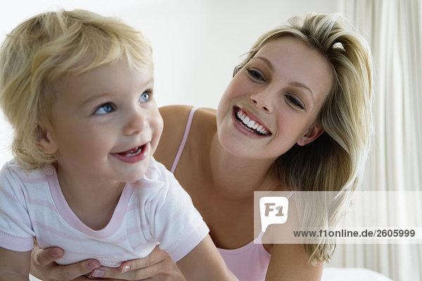 Junge Mutter hält Baby (12-24 Monate) im Bett  lachen