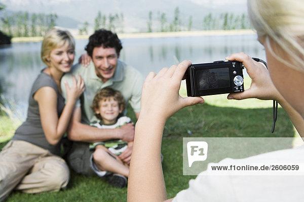 Mädchen (7-10) fotografiert Familie Mutter  Vater  Sohn vor See  lächeln