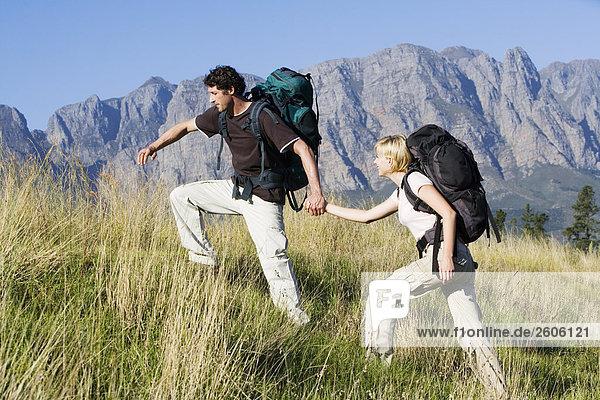 Junges Paar beim Wandern mit Rucksäcken vor Bergmassiv