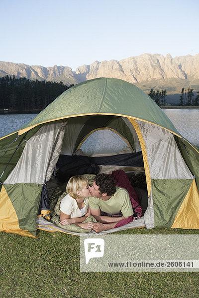 Paar beim Caming  liegt im Zelt und küsst sich  Berge und See im Hintergrund