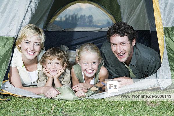Familie mit zwei Kindern beim Camping  sehen aus Zelt lachen