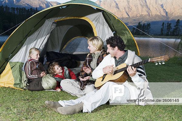 Familie mit zwei Kindern beim Camping  vor See und Bergen  Gitarre