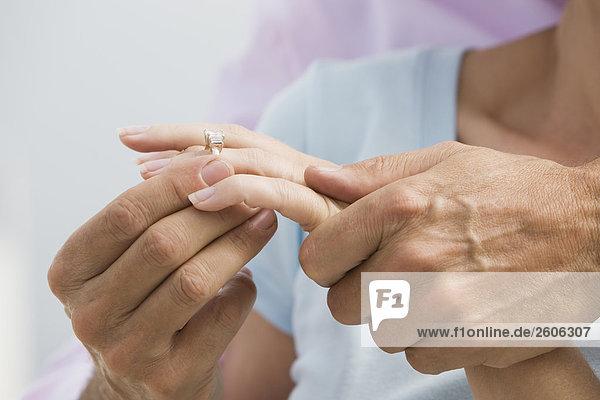 Seniorenpaar umarmt sich  Mann steckt Ring in Finger der Frau