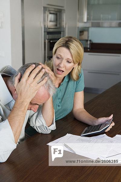 Seniorenpaar am Tisch in Küche mit Papieren Taschenrechner  verzweifelt