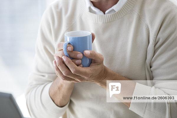 Senior trinkt ein warmes Getränk,  hält einen Becher in der Hand am Laptop