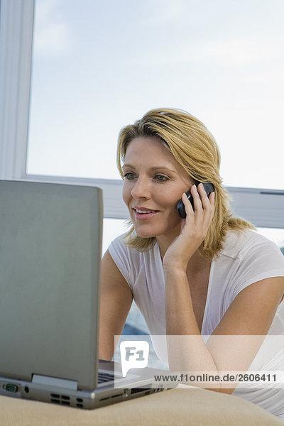 Frau telefoniert mit Handy und arbeitet am Laptop  lächelt