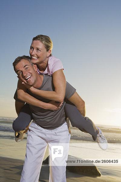 Senior couple having fun on beach  man carrying woman piggyback