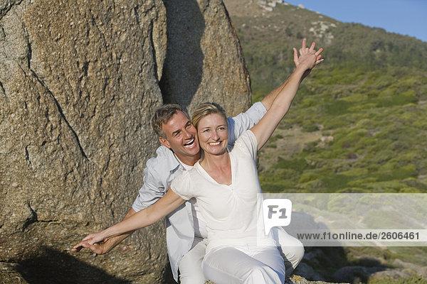 Seniorenpaar vor Felsen sitzend  Hände haltend