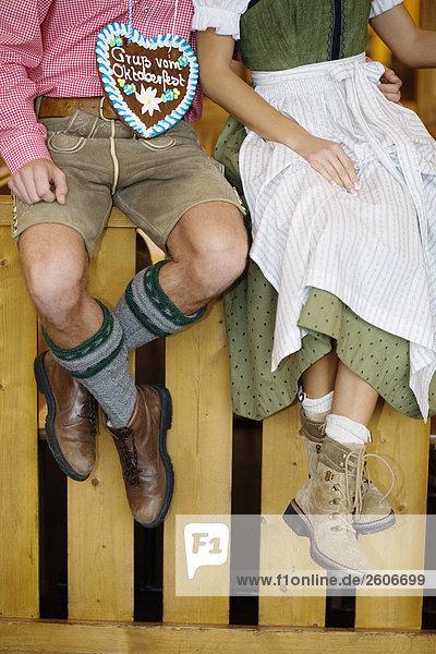 Paar in Tracht sitzt auf Holzgeländer  Mann mit Lebkuchenherz  Oktoberfest