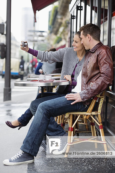 Young couple sitting at table outside cafe  woman taking photo  Paris France