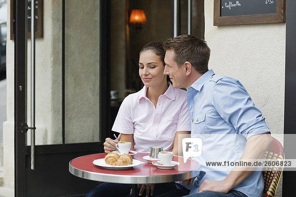 Fröhliches junges Paar sitzt draußen im Cafe  im Gespräch  Paris  Frankreich