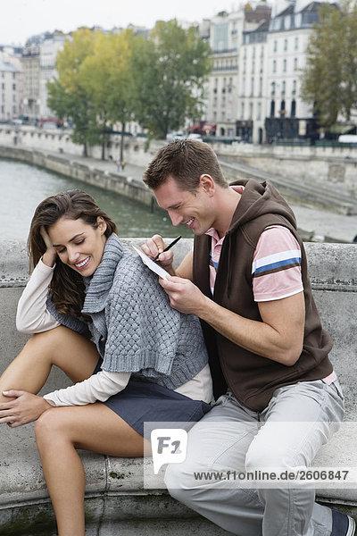 Junges Paar sitzt  Mann schreibt Postkarte auf Rücken der Frau  Paris  Frankreich