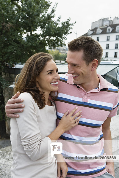 Lachendes junges Paar  Nebeneinander  Mann hält Frau im Arm  Paris  Frankreich