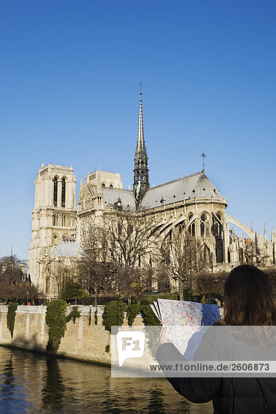 Frau liest Stadtplan vor Seine und Kathedrale von Notre Dame  Paris  Frankreich