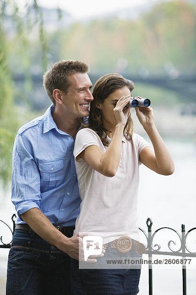 Junges Paar steht am Zaun  Frau schaut durch Fernglas  Paris  Frankreich
