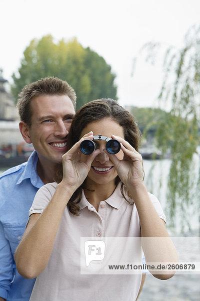 Junges Paar steht an der Seine  Frau schaut durch Fernglas  Paris  Frankreich