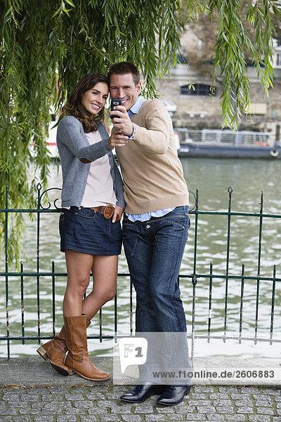 Junges Paar steht am Zaun an der Seine  fotografieren sich  Paris  Frankreich