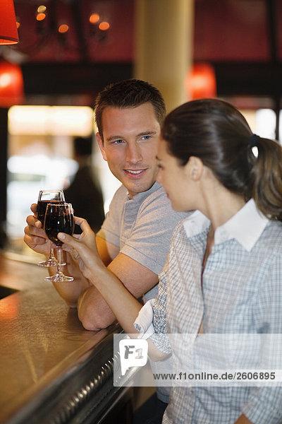 Paar prostet mit Rotwein an der Theke im Cafe  Paris  Frankreich