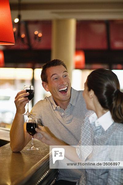 Lachendes Paar mit Rotwein flirtet an der Theke im Cafe  Paris  Frankreich