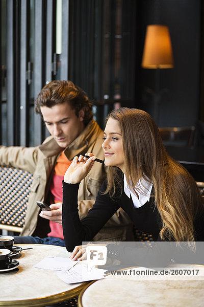 Junges Paar sitzt im Cafe  Frau schreibt  Mann mit Handy  Paris  Frankreich