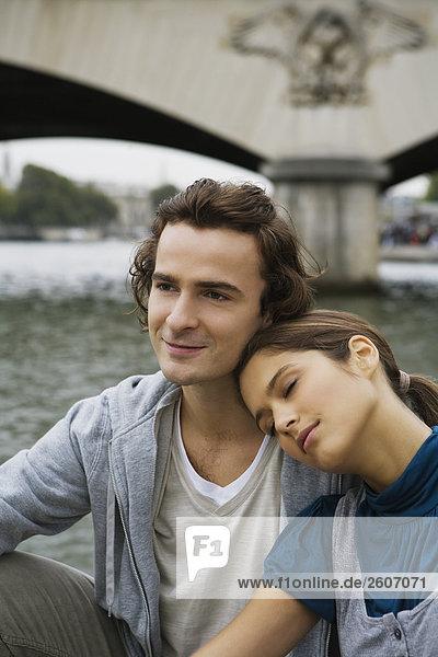Junges Paar sitzt am Ufer der Seine  Kopf auf Schulter  Paris  Frankreich