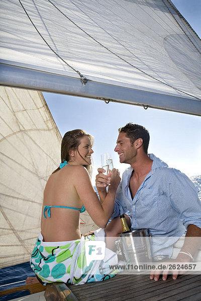 Paar trinkt Champagner auf einem Segelboot