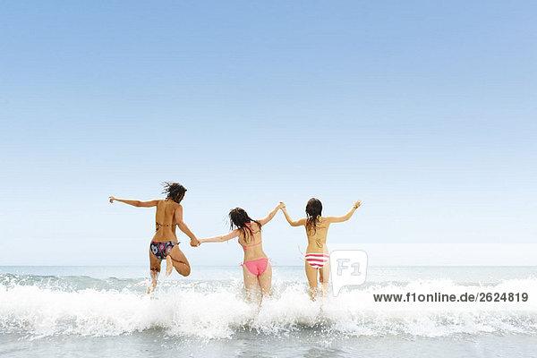 Drei Mädchen springen über die Welle Drei Mädchen springen über die Welle