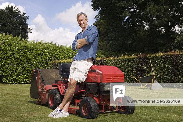 Portrait Mann steht am Rasenmäher
