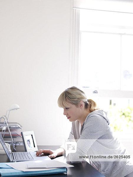 Frau arbeitet im sonnigen Home-Office