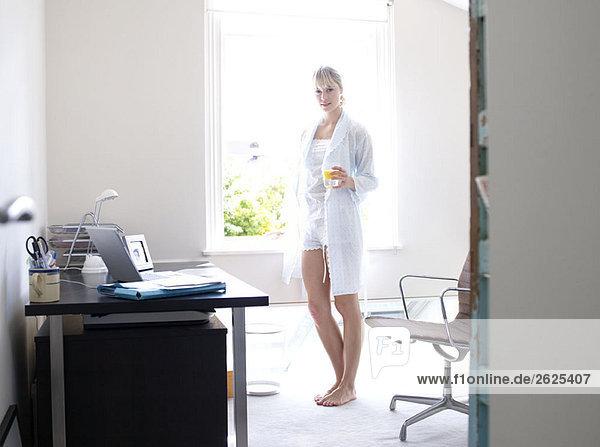Frau steht im sonnigen Home-Office