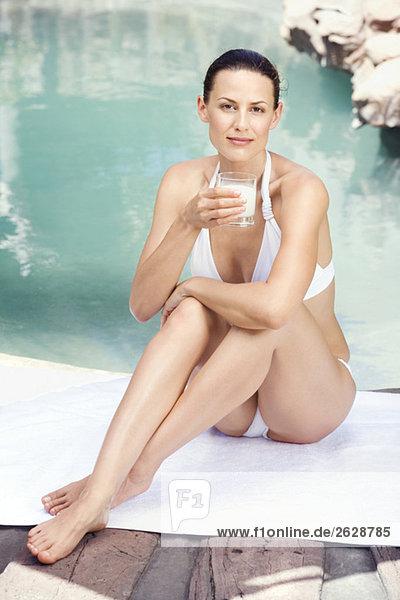 Junge Frau im Bikini mit einem Glas Milch