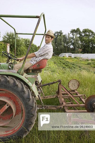 Landwirt auf dem Traktorpflugfeld
