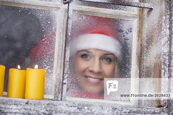 Austria  Salzburger Land  Young woman looking through window  candles on windowsill