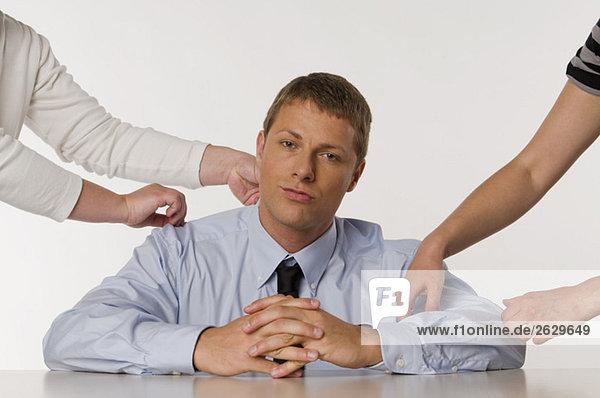 Geschäftsmann sitzend  Hände von zwei Personen  die ihn berühren