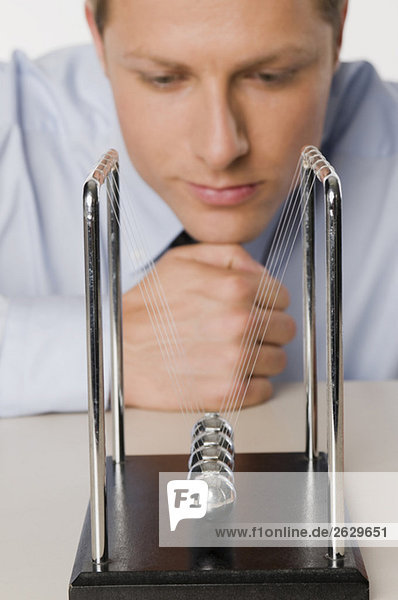 Businessman meditating  Newtons' Cradle in the foreground