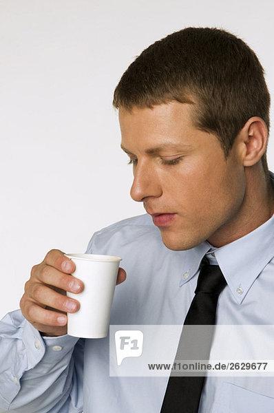 Geschäftsmann hält Tasse Kaffee  Porträt