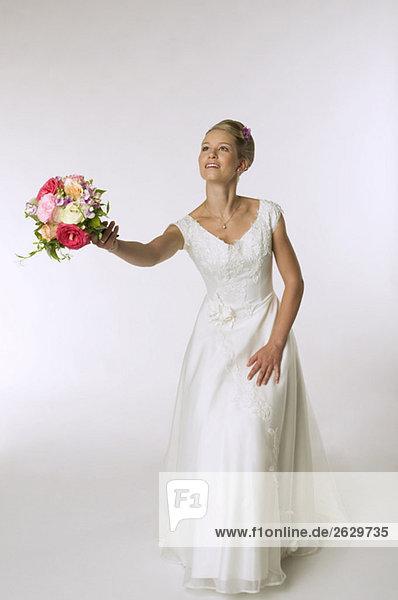 Junge Braut wirft Brautstrauß