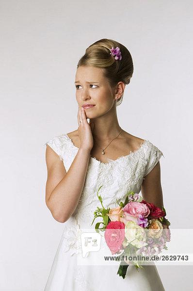 Junge Braut mit Brautstrauß  Hand an Kinn  Porträt