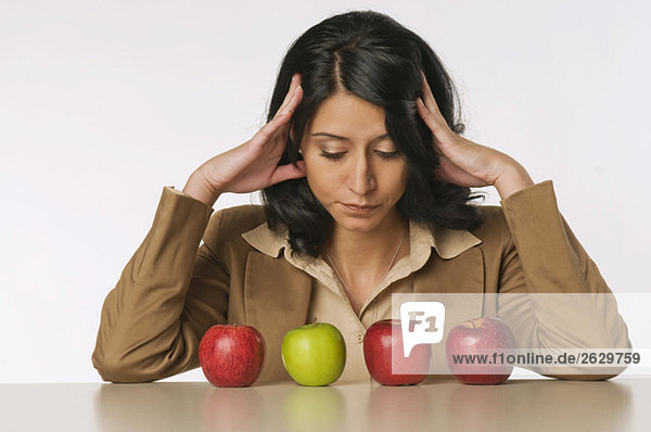 Junge Frau schaut Äpfel an  nachdenklich  Portrait