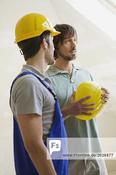 Zwei Männer mit Schutzhelmen auf der Baustelle