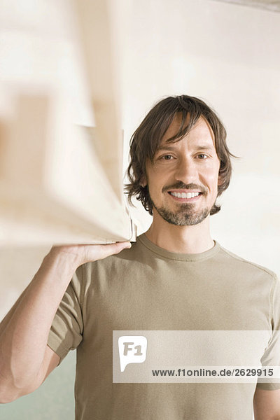Young man holding lumber  smiling  portrait  close-up