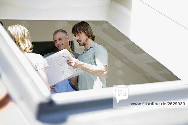 Junges Ehepaar und Architekt konferieren auf der Baustelle