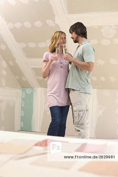 Junges Paar auf der Baustelle mit Sektgläsern