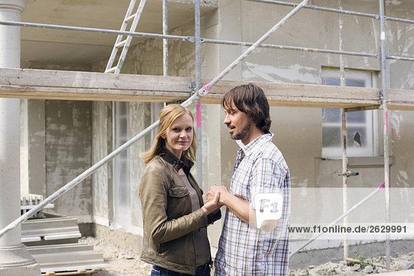 Junges Paar vor dem Haus im Bau