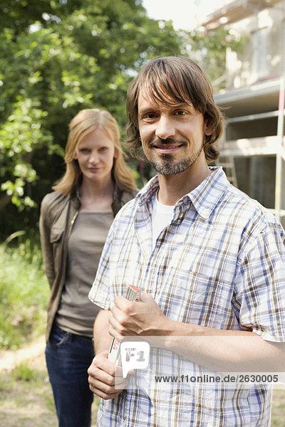 Junges Paar  Mann mit Zollstock  lächelnd  Porträt